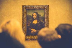 Des personnes contemplent la peinture de la Joconde dans le musée du Louvres