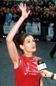 Julia Roberts lève le bras lors de la première du film Coup de foudre à Notting Hill et laisse apparaître une aisselle non épilée