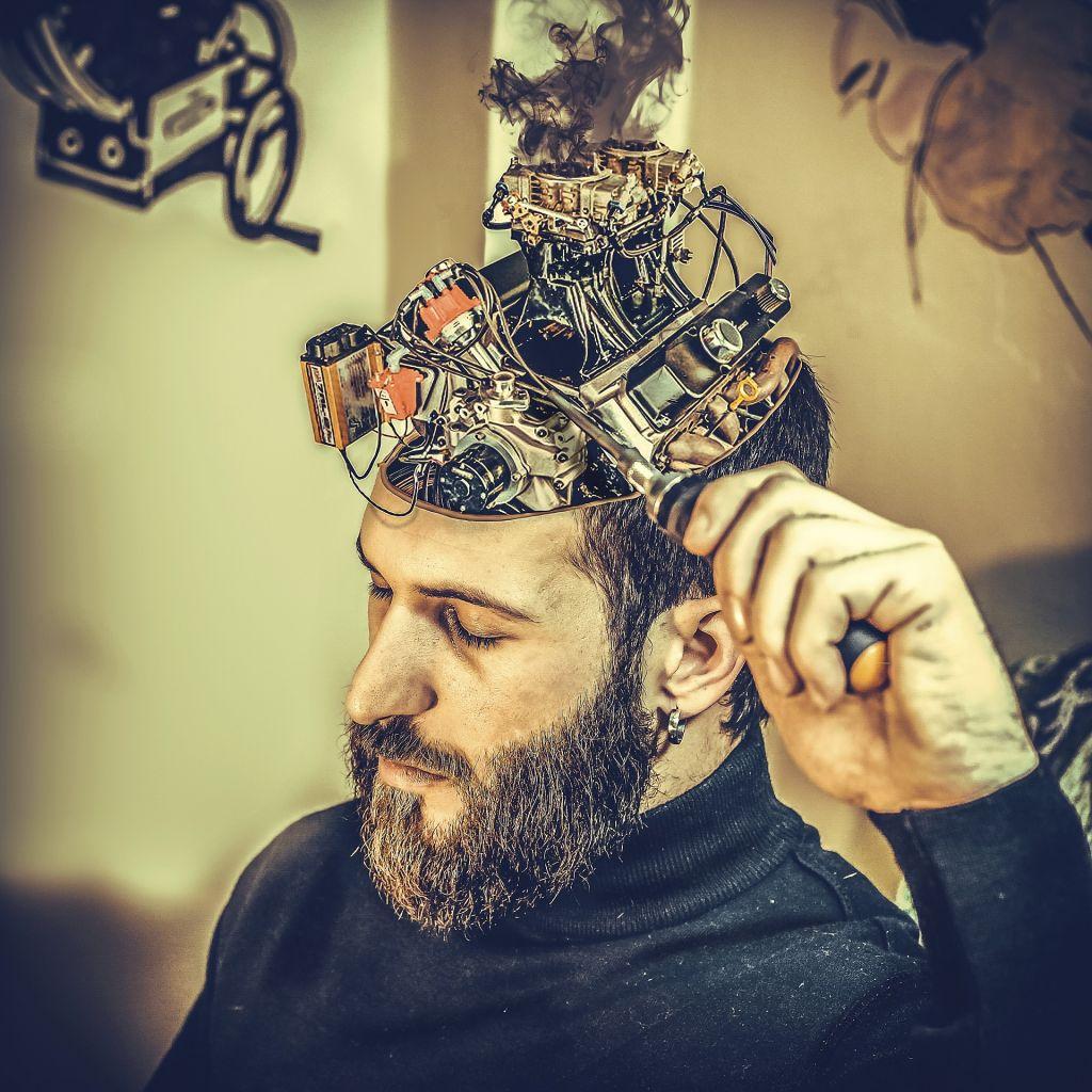homme barbu, de 3 quarts, les yeux fermes, porte un pull a col roule noir. Sa tete est decalottee pour laisser voir la mecanique de son cerveau.