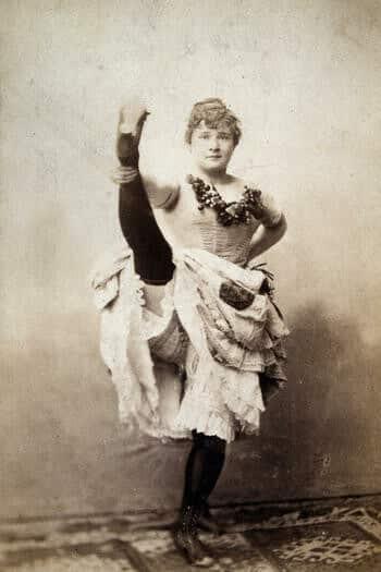 Photographie en noir et blanc de La Goulue qui lève la jambe dans un studio de photographie.